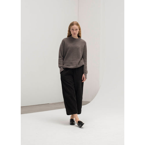 light brown long sleeve sweater worn with black wide legged pants