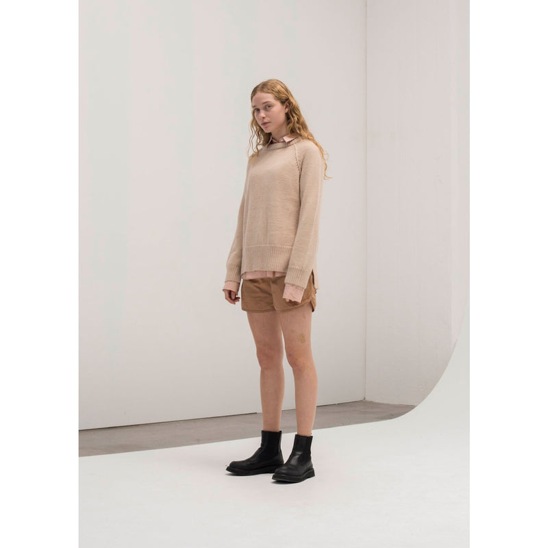 model wearing a light pink chunky sweater with tan shorts and black boots