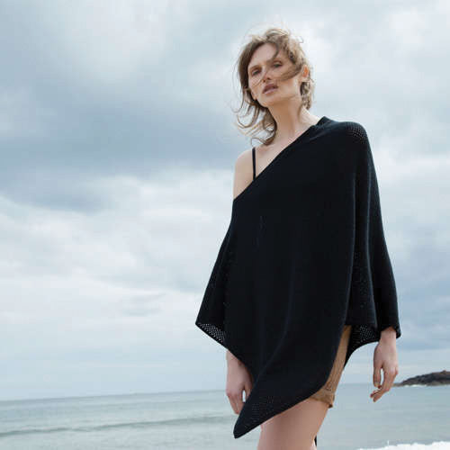 Woman wearing cashmere poncho at the beach
