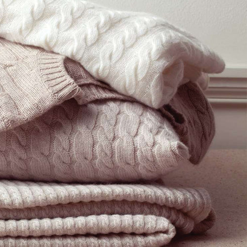 pile of cashmere jumpers for a blog about why not all cashmere is created equal