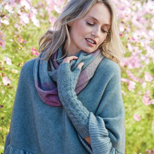 girl wearing possum merino silk poncho and long wrist warmer and snood in flowery field