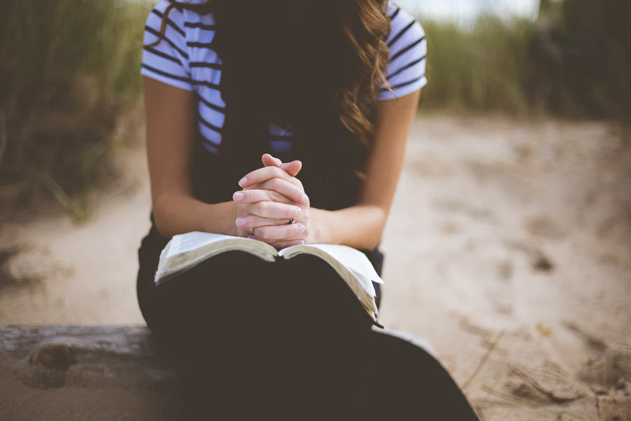 Woman praying with a bible outdoors