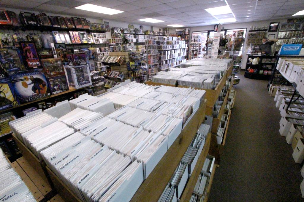 A walkway featuring comic book displays inside the Mythical Mountain store.