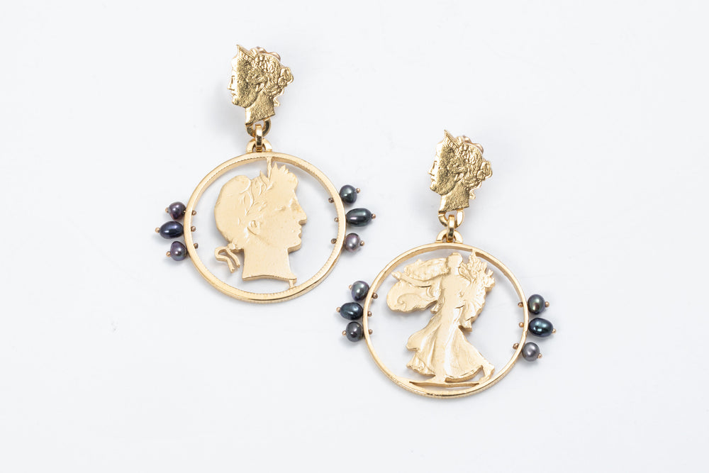 A pair of gilded coin earrings by artist Stacey Lee Weber.