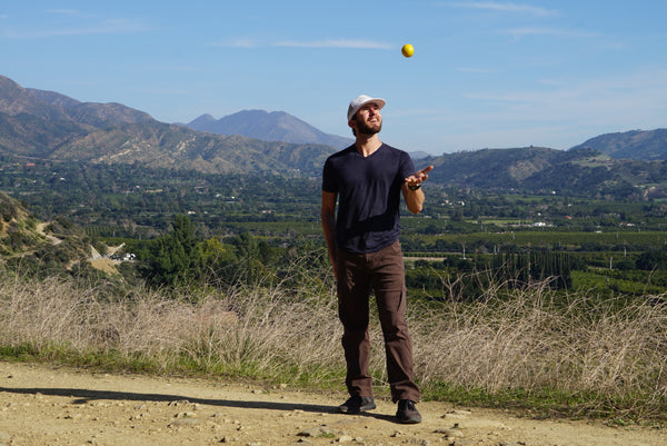 Stephen tossing a ball in front of a mountain landscape