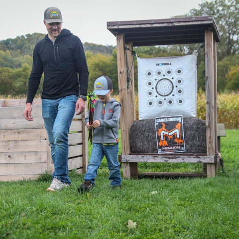 Tom with his son, teaching him archery