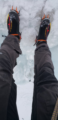 Ice climbing boots with spikes on an ice climb