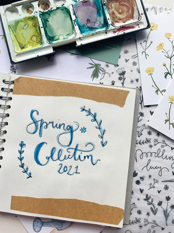 Spring collection sketchbook open on a table with paints