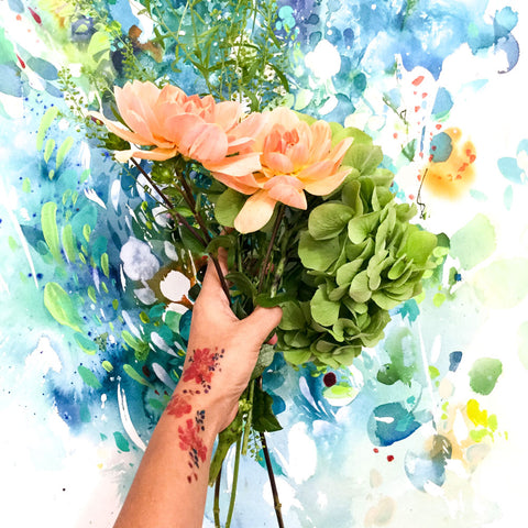 Holding flowers with a floral tattoo and a turquoise painting by watercolour artist CreativeIngrid | Ingrid Sanchez.