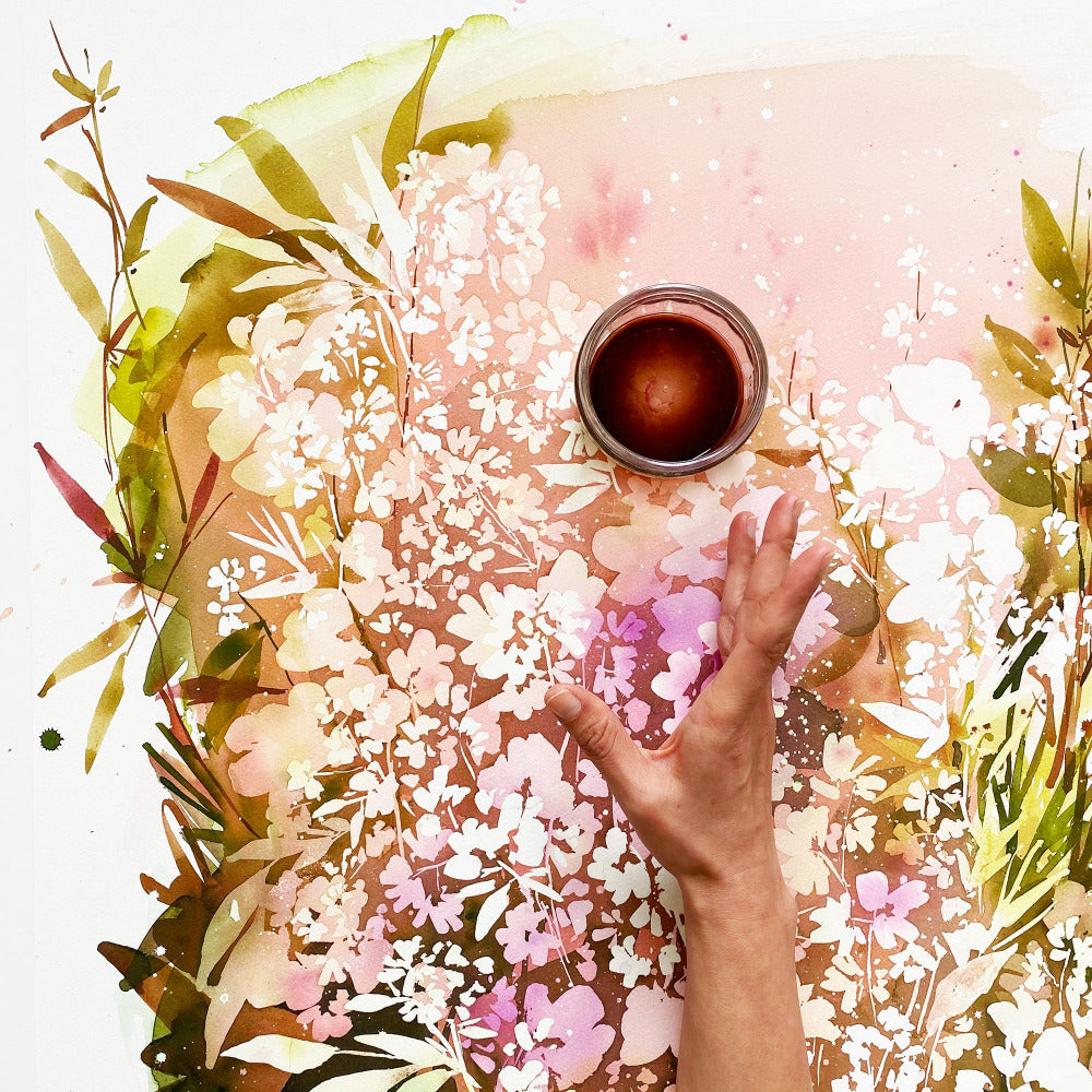 Hand of artist Ingrid Sanchez holding a watercolor palette over a painting of white pink flowers.  'Ground Spell Garden', Ingrid Sanchez, CreativeIngrid. London 2021.