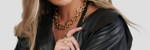 a model wearing 14k gold chain necklaces and 14k gold and diamond rings