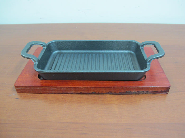 Large rectangular cast iron sizzling with wooden base