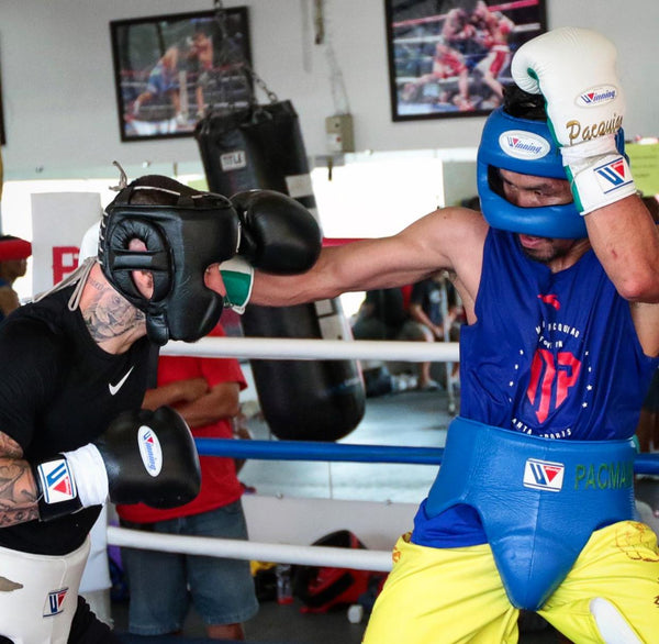 Boxing sparring between two elite boxers both using Winning boxing equipment. Headgear, gloves, and cup.