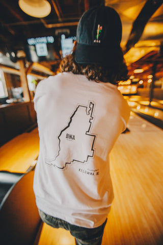 Photo of a person wearing a white, long-sleeved shirt with an outline of the Kelowna city limits on the back.