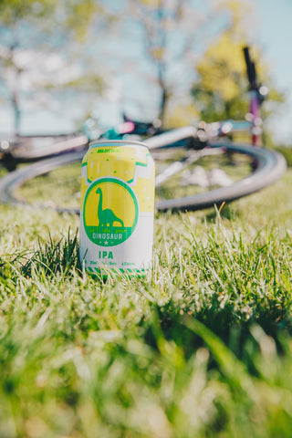 "Photo of a can of ""Don't Lose Your Dinosaur"" beer. This is the name of our IPA. The can of beer is on the grass beside a bicycle laying on its side."