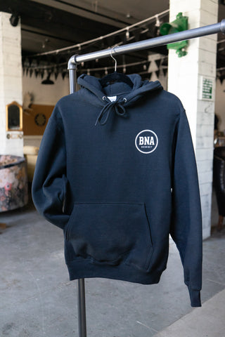 Photo of a black hoodie on a hanger. A small, white BNA logo is on the left chest.