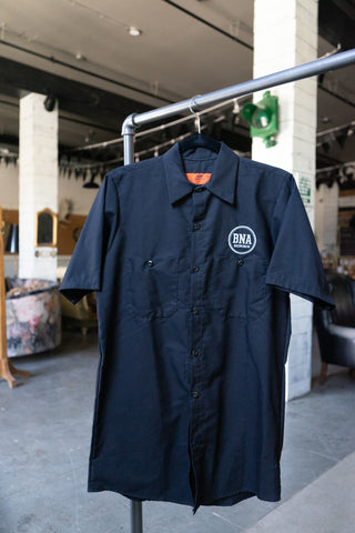 "Photo of a black ""work shirt."" A collared, short-sleeve, button-up shirt, with the BNA logo on the left chest."