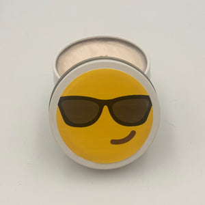 A natural wax candle in a small travel size tin with an emoticon with cool sunglasses and a smirk on the top lid.