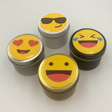 Four candle tins in black, white, silver and gold with emoji label design cry laughing, love hearts, smiley face