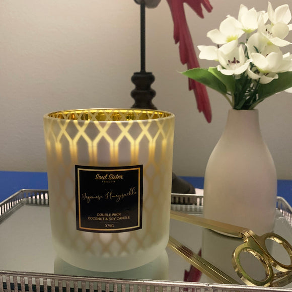 Gold patterned candle lit and showing ambience, gold lettering on black luxury label with gold wick trimmers on a silver tray and styled flower vase