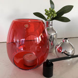 A red melt burner styled with a black candle snuffer and two silver vases; the oil burner is vibrant transparent red with a deep bowl and an opening at base for a tea light candle