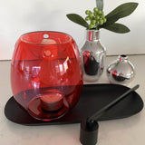 A red melt burner styled with a black candle snuffer and black candle trayand two silver vases; the oil burner is vibrant transparent red with a deep bowl and an opening at base for a tea light candle