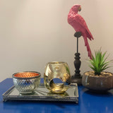 Silver wax melt bowl with orange inner metallic, gold melt burner with silver wick dipper on a silver decorative decor tray with pink parrot atop perch and plant pot