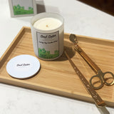 White candle and lid on a wooden board with wick dipper and wick trimmers in gold and a white carry box