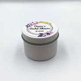 Personalised white candle party favour with custom text, design wreath in purple theme with lilac florals, cursive text