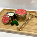 Gold Christmas candle tins with Red Bauble label design and personalised text with gold wick trimmers resting on wooden tray
