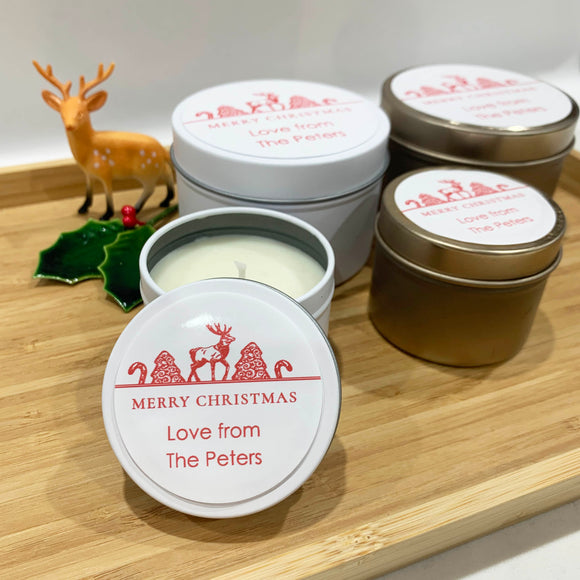 White and gold Christmas candle tins in two sizes with red reindeer and ornaments labels on a white background, personalised text
