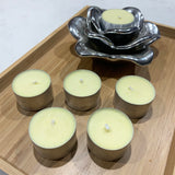 Scented tea light candles, coloured lemon pastel yellow in a silver candle holder