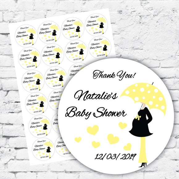 Baby shower gift labels personalised with name, pregnant woman in cute bow maternity top carrying polka dot yellow umbrella, yellow pants and black boots. Neutral baby colour yellow. white background with black text