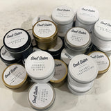 Assorted silver, white, black and gold small tin candles, labelled on top of the lid in white with black text