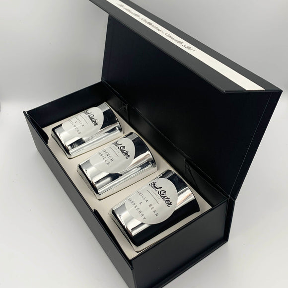 Silver mini candles white labels laid out in a black lined gift box with magnetic closure