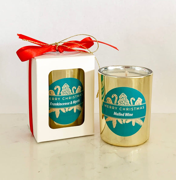 Small gold mini candle gift in white box with red Christmas ribbon