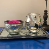 Silver melt and oil burner on a silver footed designer tray with a silver metal bowl lined with hot pink
