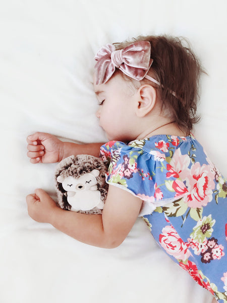 Little girl wearing blush velvet bow, sleeping
