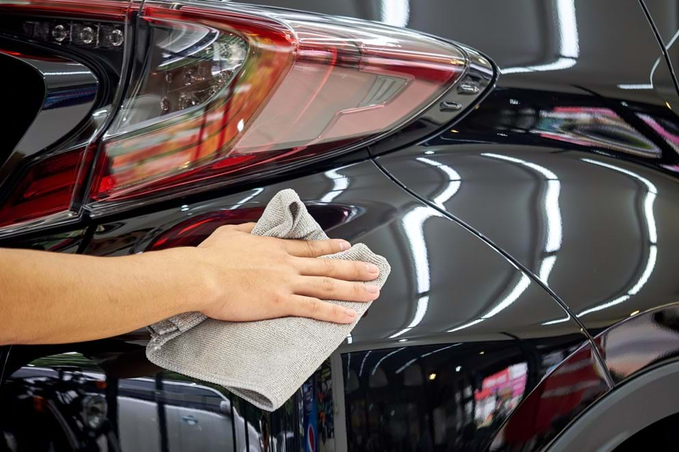 man removing wax from car surface with a microfiber cloth for shiny finish - turtle wax