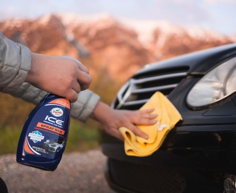 turtle wax ice spray wax being used on a black car to wax the surface with a microfiber towel