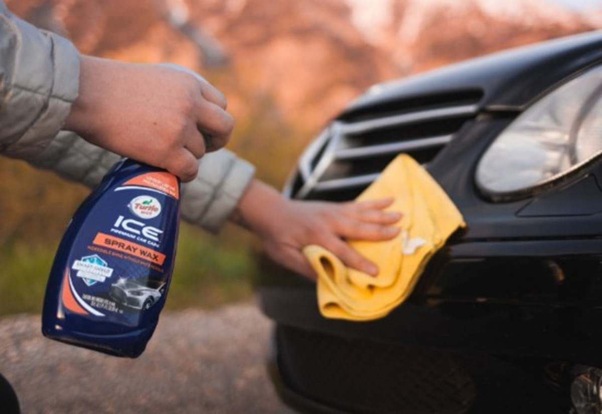 turtle wax ice spray wax being applied on a black car following car scratch repair process to renew the shine