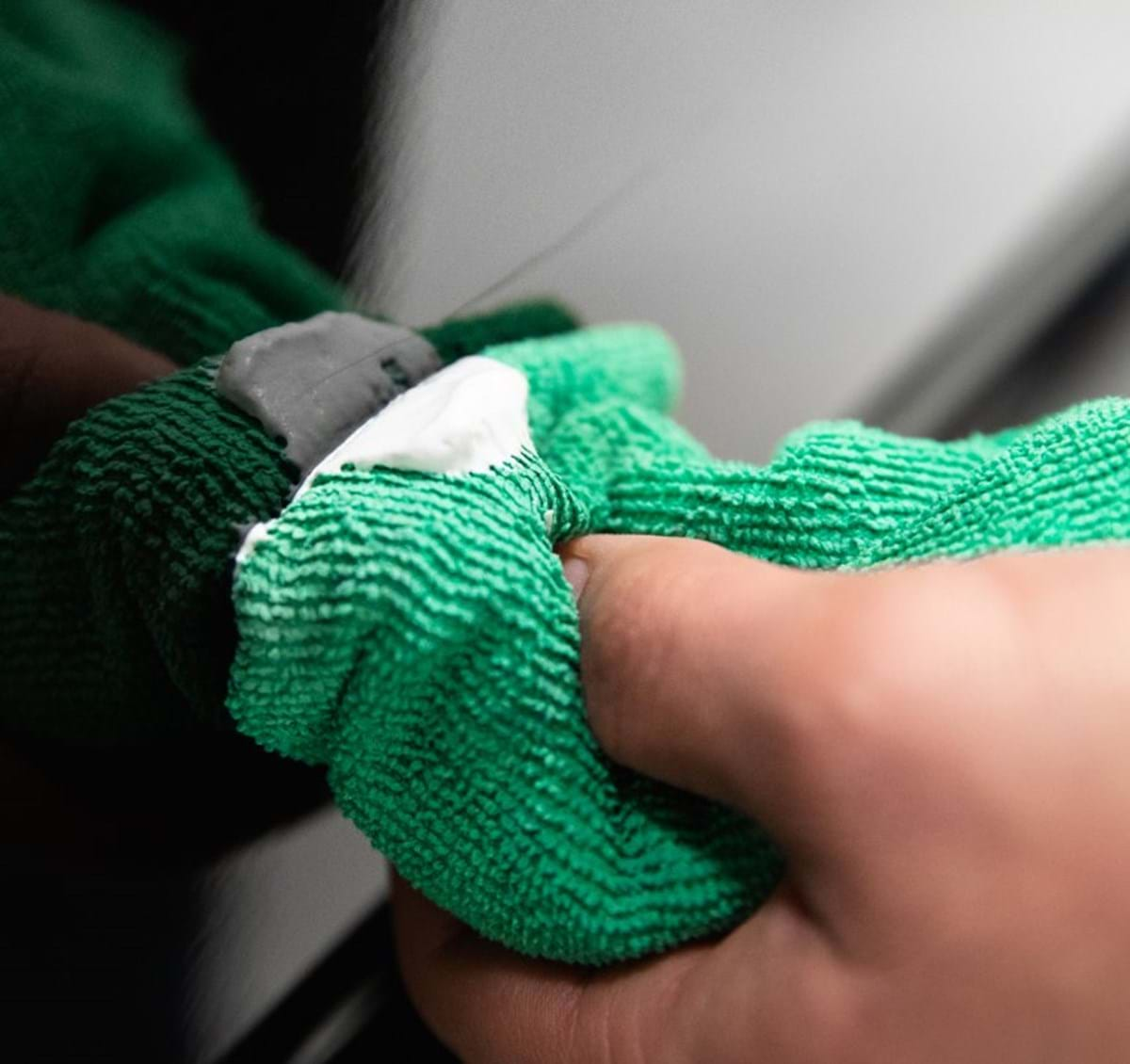 turtle wax scratch repair and renew being applied with a green microfiber cloth on a scratched black car paint