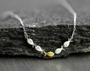 Swimming against the current. Dainty silver necklace. School of fish with one golden color fish swimming upstream. Gift for her.