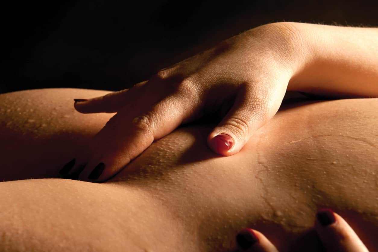 Woman giving herself a yoni massage