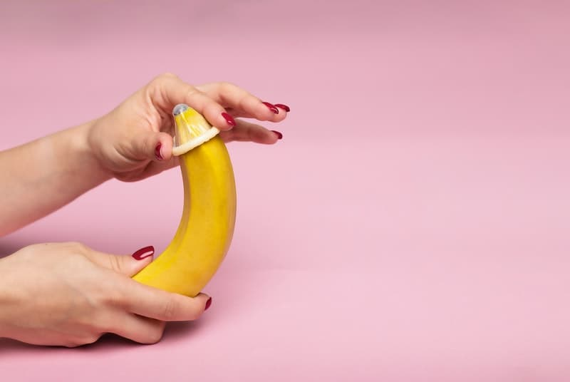 Condom being put on an unpeeled banana