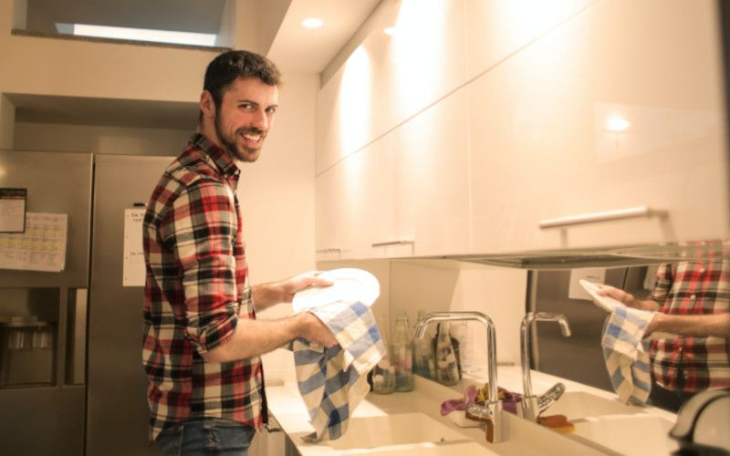 A man doing chores around the house to attempt to arouse his female partner