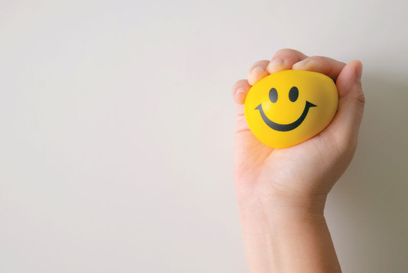 Happy face ball being squeezed to represent happiness from squeeze technique