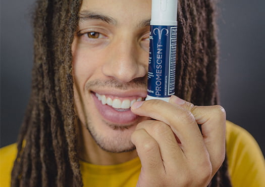 A man holding Promescent delay spray up to his face while smiling and looking into the camera.