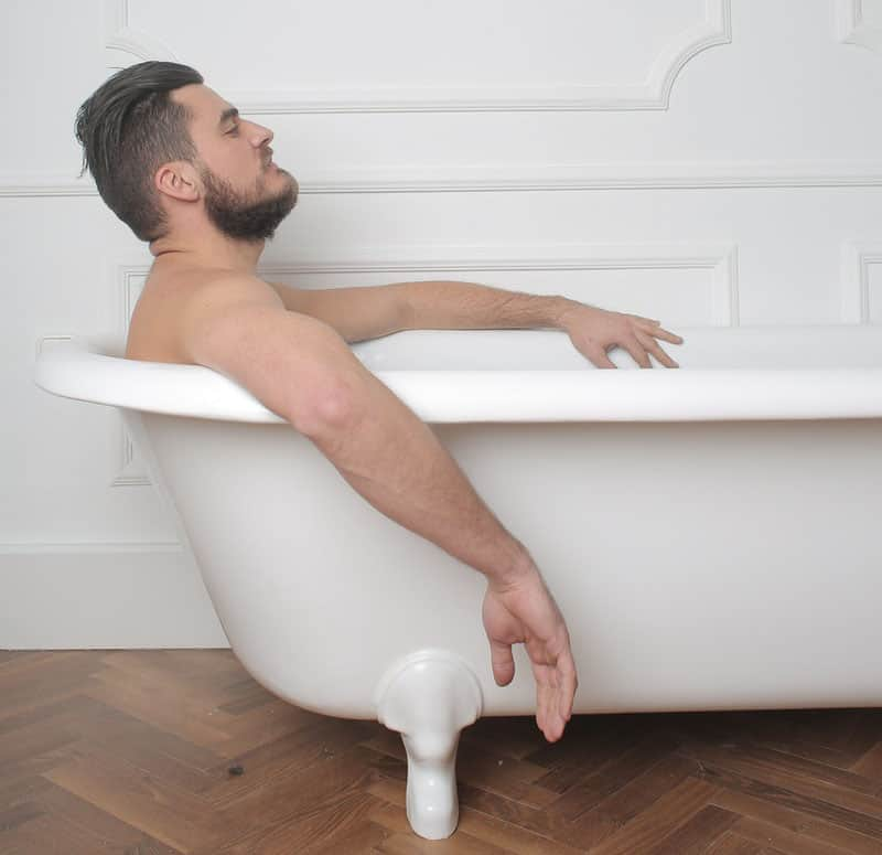 Man in bathtub cleaning to prevent smegma