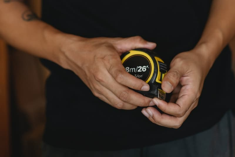 Man holding tape measure to measure the success of jelqing